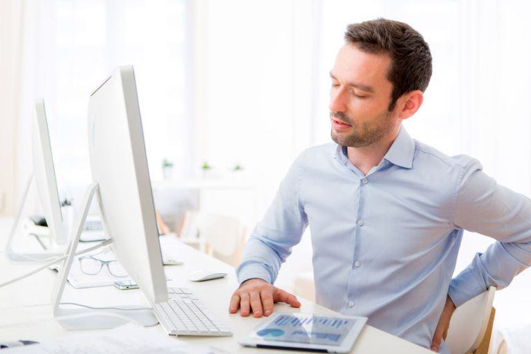 man with hurting back at computer
